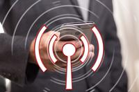 wi fi logo over image of person holding mobile phone